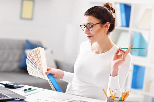 Jonge vrouw die in haar kantoor aan huis werkt