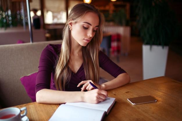 Jonge vrouw die in haar notitieboekje in koffie schrijft