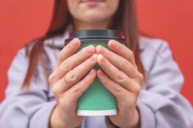 Jonge vrouw die in handen koffieglas houdt