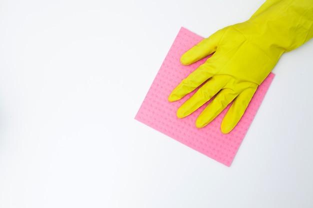 Jonge vrouw die in handschoenen bureaulijst schoonmaken