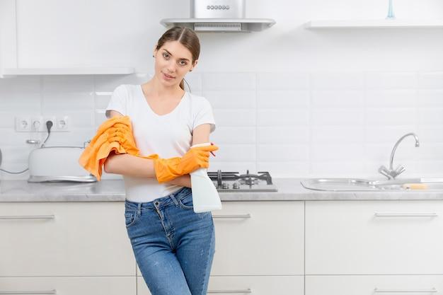 Jonge vrouw die in handschoenen voor het schoonmaken van keuken voorbereidingen treffen