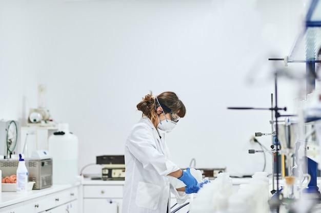 Jonge vrouw die in het laboratorium werkt. ze draagt een masker, een veiligheidsbril en veiligheidshandschoenen en ze giet een monster in een glas voor analyse