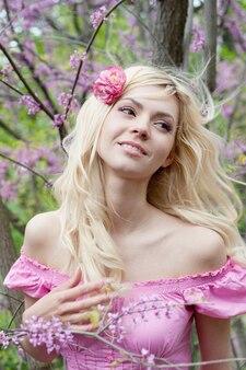 Jonge vrouw die in het lentepark droomt