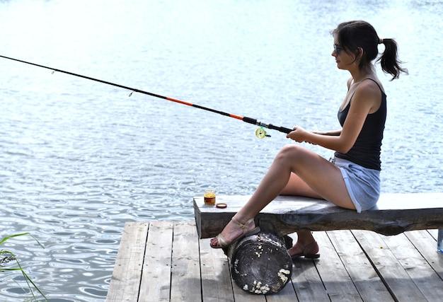 Jonge vrouw die in het meer vist en op een houten pier zit