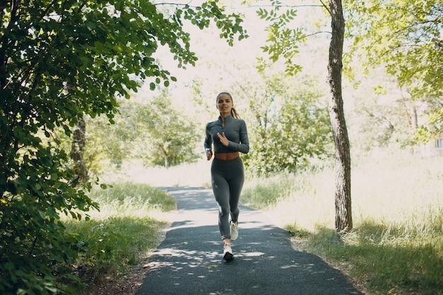 Jonge vrouw die in het park loopt