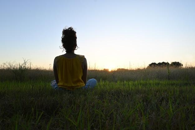 Jonge vrouw die in het veld zit en de zonsondergang overweegt