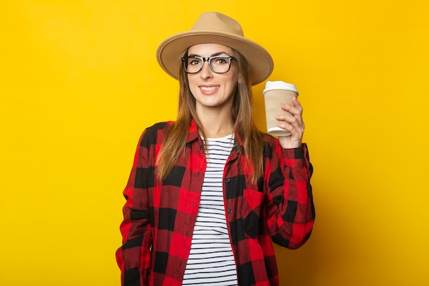Jonge vrouw die in hoed en plaidoverhemd document kop met koffie op geel houdt