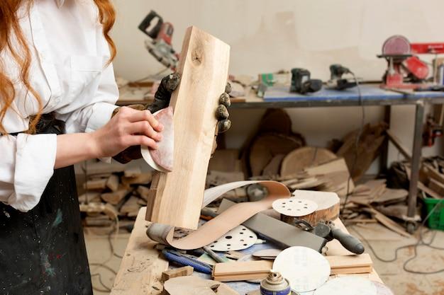Jonge vrouw die in hout vervaardigt