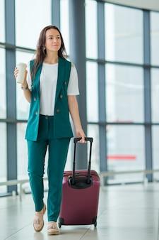 Jonge vrouw die in internationale luchthaven met haar bagage en koffie loopt om te gaan