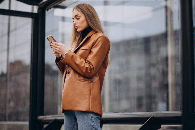 Jonge vrouw die in jas in de stad loopt