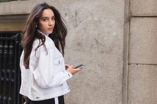Jonge vrouw die in jasje over schouder kijkt die de mobiele telefoon in hand houdt