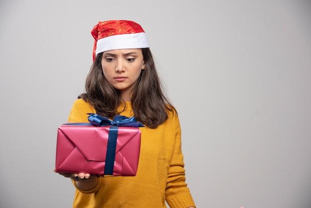 Jonge vrouw die in kerstmanhoed een giftdoos bekijkt.