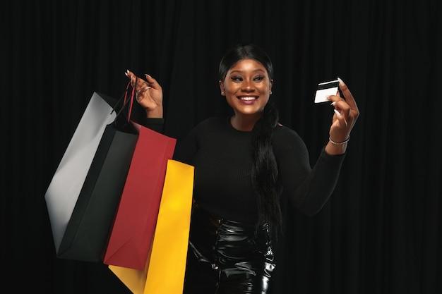 Jonge vrouw die in kleding op zwart winkelt