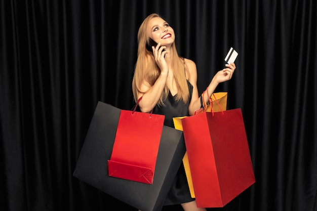 Jonge vrouw die in kleding op zwarte muur winkelt