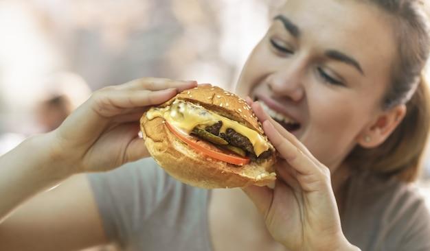 Jonge vrouw die in koffie smakelijke sandwich eet