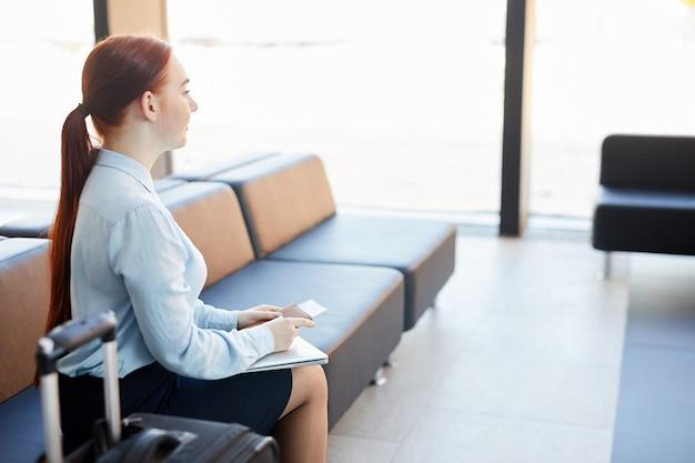 Jonge vrouw die in luchthaven wacht