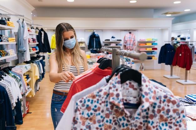 Jonge vrouw die in masker bij een kledingsopslag winkelen in de pandemie van het coronavirus