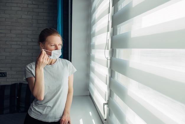 Jonge vrouw die in masker door de blinds kijkt. in quarantaine geplaatste coronaviruspersoon. blijf thuis. stop de pandemie. zelfisolatie, masker ophangen
