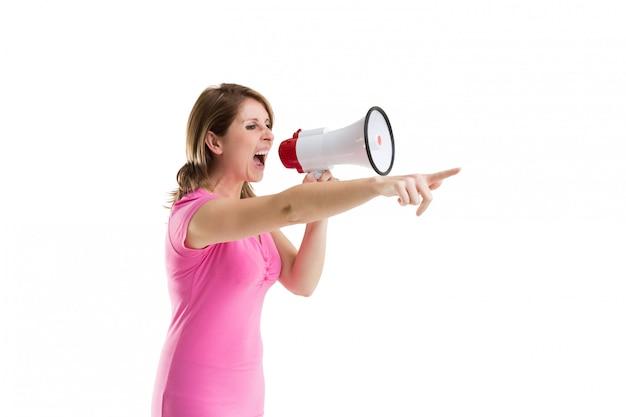 Jonge vrouw die in megafoon schreeuwt aangezien zij gebaren
