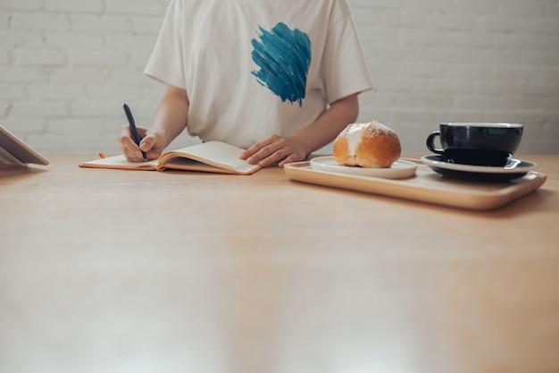 Jonge vrouw die in notitieboekje in koffiewinkel schrijft
