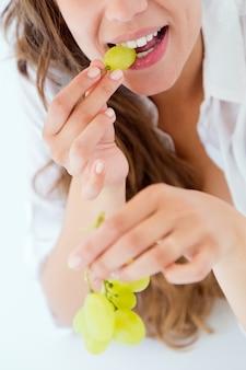 Jonge vrouw die in ondergoed druiven eet. geïsoleerd op wit.