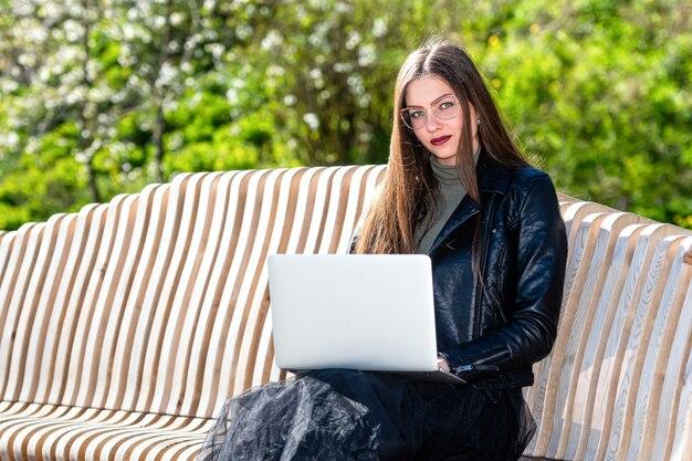 Jonge vrouw die in oogglazen op bank in park met laptop zitten