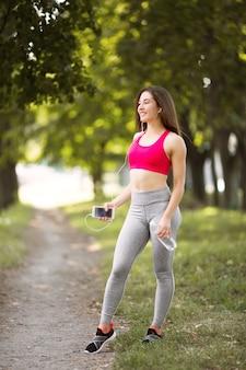 Jonge vrouw die in openlucht in park met fles water en telefoon in handen loopt.