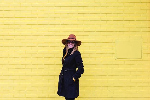 Jonge vrouw die in openlucht mobiele telefoon en het glimlachen gebruikt. lifestyle in de stad. gele bakstenen muur