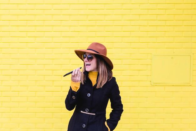 Jonge vrouw die in openlucht mobiele telefoon met behulp van en audio verzendt. lifestyle in de stad. gele bakstenen muur