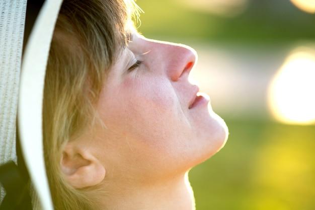 Jonge vrouw die in openlucht op zonnige de zomerdag ontspant. gelukkige dame in het dagdromen van de strohoed het denken. het kalme mooie glimlachende meisje dat van verse lucht geniet ontspant met gesloten ogen.