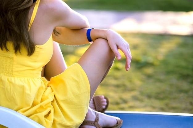 Jonge vrouw die in openlucht op zonnige de zomerdag ontspant. gelukkige damezitting bij het groene dagdromen van het grasgazon het denken. rustig meisje genieten van frisse lucht ontspannen en mediteren.