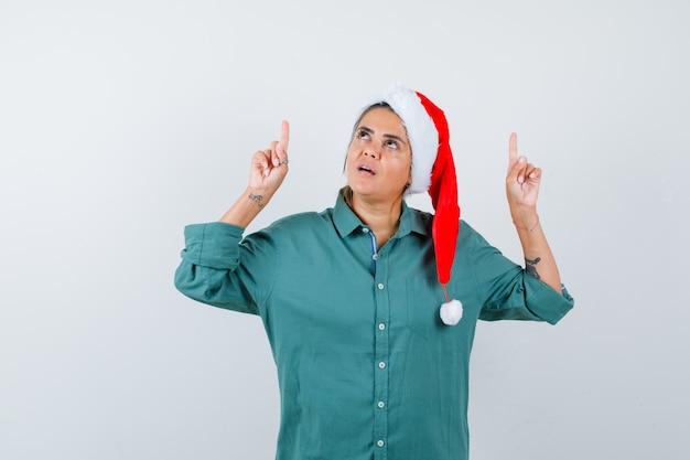 Jonge vrouw die in overhemd, kerstmuts omhoog wijst en er zelfverzekerd uitziet, vooraanzicht.