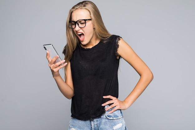 Jonge vrouw die in overhemd op telefoon schreeuwt isoleerde grijze achtergrond