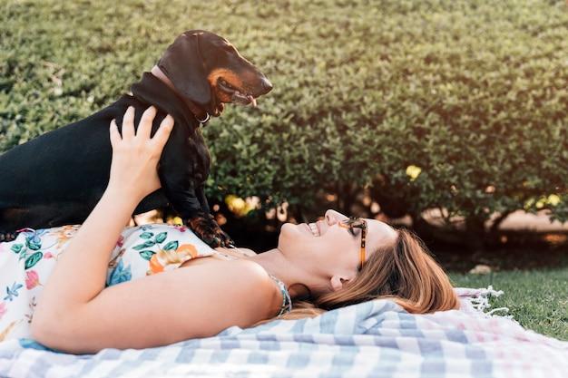 Jonge vrouw die in park met haar hond ligt
