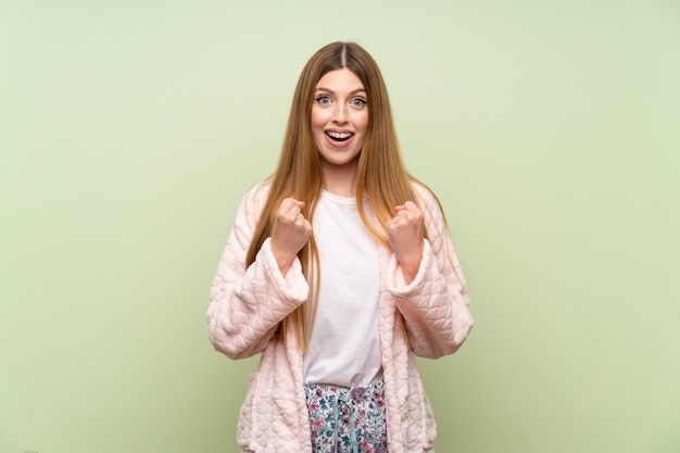Jonge vrouw die in peignoir over groene muur een overwinning viert