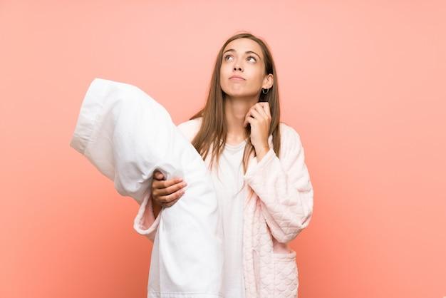 Jonge vrouw die in peignoir over roze muur een idee denkt