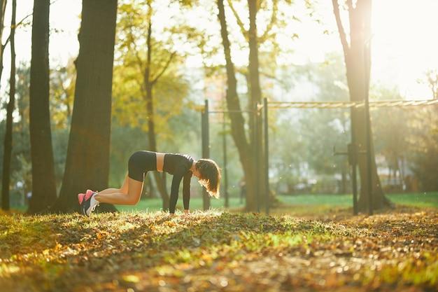 Jonge vrouw die in pilates bij stadspark presteert