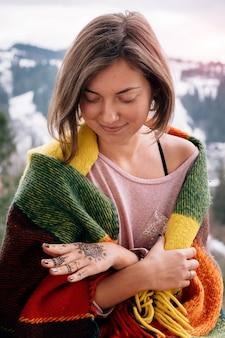 Jonge vrouw die in plaid dichtbije mehndi kijkt