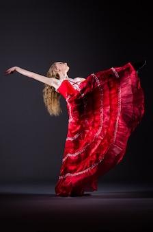 Jonge vrouw die in rode kleding danst