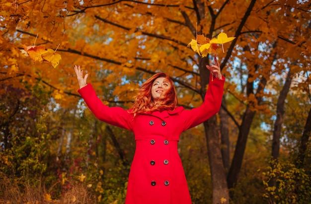 Jonge vrouw die in rode laag bladeren in het bos werpt