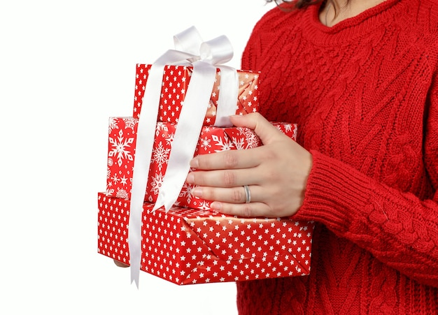 Jonge vrouw die in rode sweater giftdozen in handen houdt die op wit worden geïsoleerd