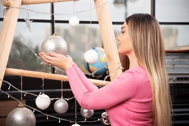 Jonge vrouw die in roze sweater een gouden kerstmisbal houdt. hoge kwaliteit foto