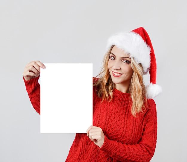 Jonge vrouw die in santahoed leeg witboek cholding