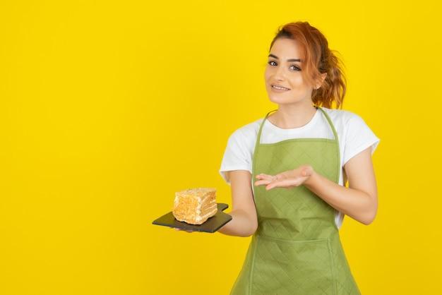 Jonge vrouw die in schort cakeplak met hand op gele muur houdt