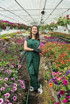 Jonge vrouw die in serre werkt die voor bloemen zorgt