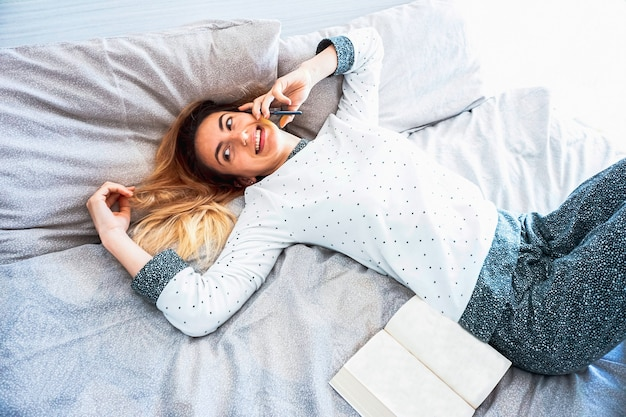 Jonge vrouw die in slaapkamer verblijft die aan de telefoon spreekt