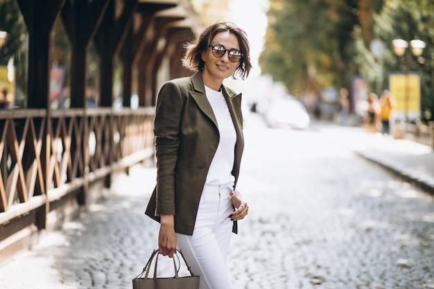 Jonge vrouw die in stad in zonnebril loopt