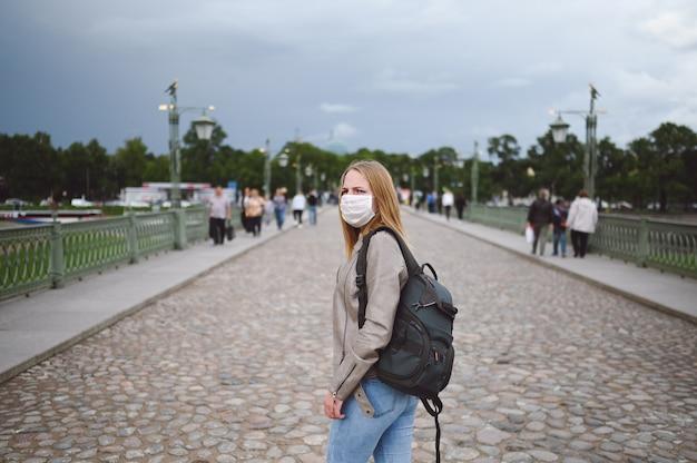 Jonge vrouw die in stadsstraat tussen de menigte loopt met rugzak die een beschermend gezichtsmasker draagt voor de preventie van covid 19