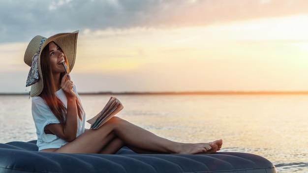 Jonge vrouw die in strohoed poëzie op het strand samenstelt. inspiratie concept