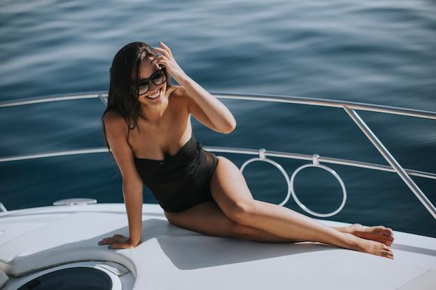 Jonge vrouw die in swimwear en zonnebril op een jachtdek zit